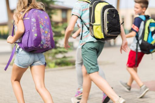 Néhány iskolás gyerek iskolába siet.