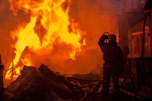 A tűzoltó egy égő házat próbál eloltani.