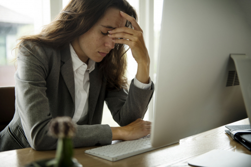 Egy nő szomorúan ül az irodájában. Kirúgták.