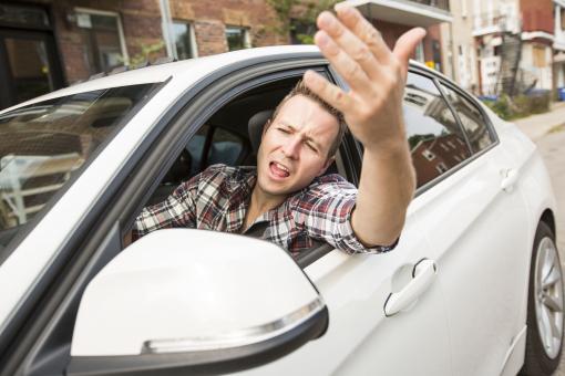 Egy fiatal férfi autót vezet és ordibál az ablakon.