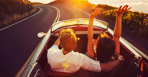 Pár autózik a naplementében