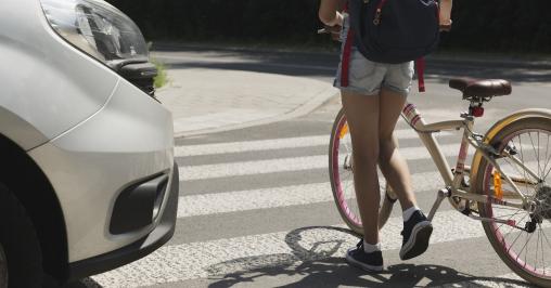 lány tolja át a kerékpárját a zebrán