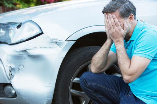 Férfi fogja a fejét a sérült autója mellett